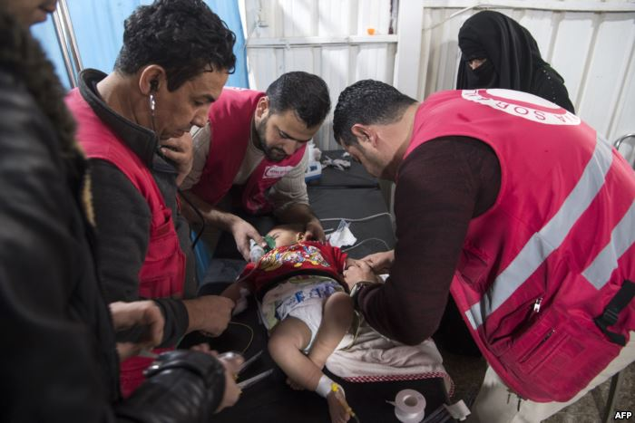 Syrian medics treat a baby at a makeshift clinic at the internally displaced