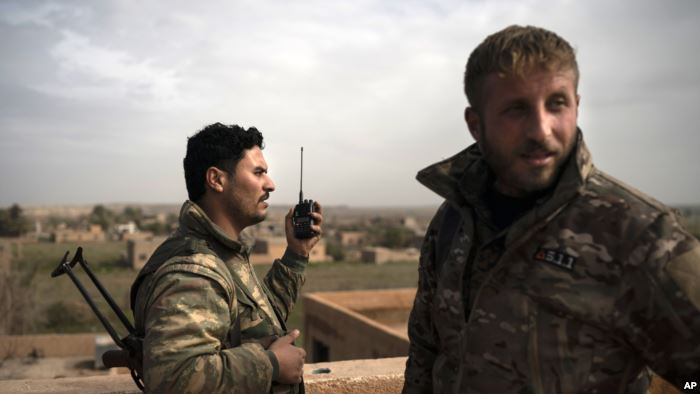 U.S.-backed Syrian Democratic Forces (SDF) fighters talk on a radio in a roof