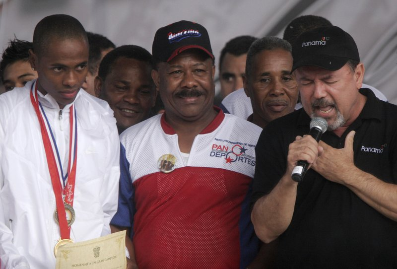 FILE - In this Aug. 21, 2008 file photo, boxing champion Eusebio Pedroza attends a celebration ceremony flanked by Olympic athlete Irving Saladino and Ruben Blades, in Panama City. (AP Photo/Arnulfo Franco, File)