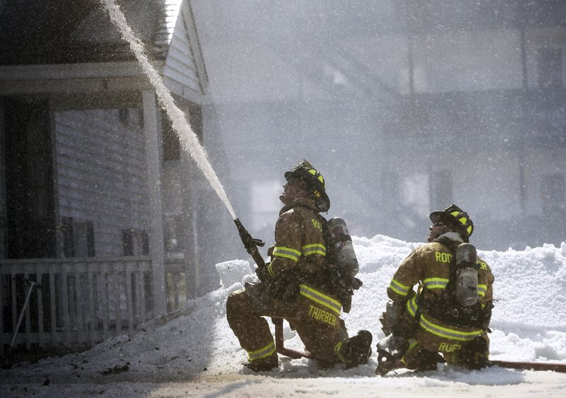 Rochester firefighter Tyler Thurber, left, and Micah Ruel work to bring a blaze under control as they battling a four-alarm fire at a three-story apartment building, Friday, March 1, 2019, in Berwick, Maine. (Deb Cram/Foster's Daily Democrat via AP)