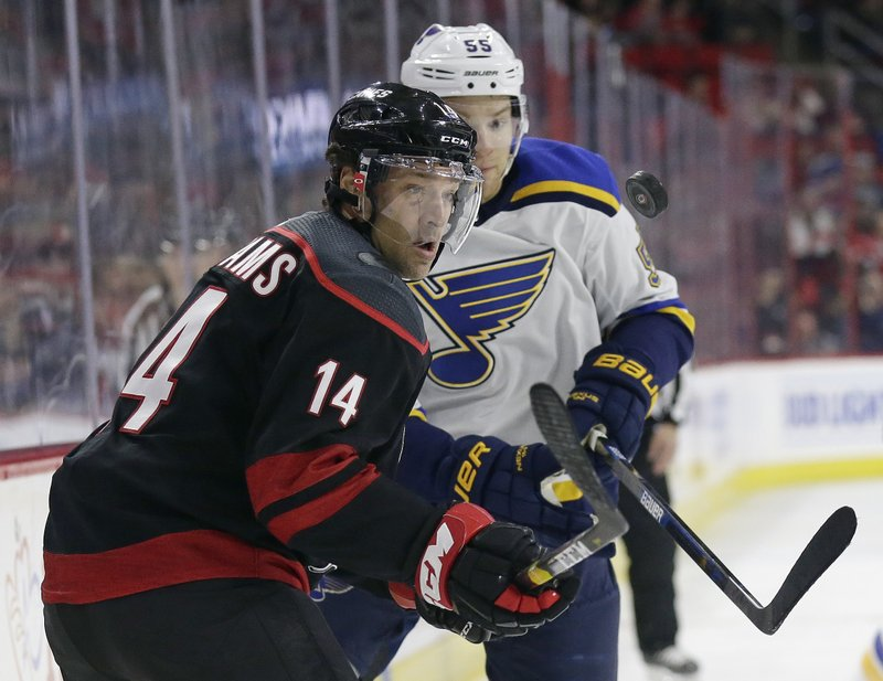 Carolina Hurricanes' Justin Williams (14) keeps an eye on the puck while skating with St. Louis Blues' Colton Parayko (55) during the first period of an NHL hockey game in Raleigh, N. (AP Photo/Gerry Broome)