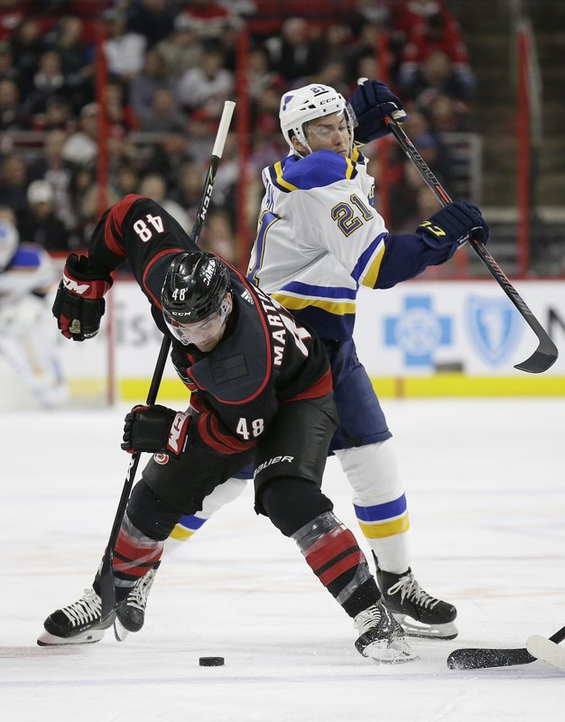 Carolina Hurricanes' Jordan Martinook (48) and St. Louis Blues' Tyler Bozak (21) struggle for possession of the puck during the first period of an NHL hockey game in Raleigh, N. (AP Photo/Gerry Broome)