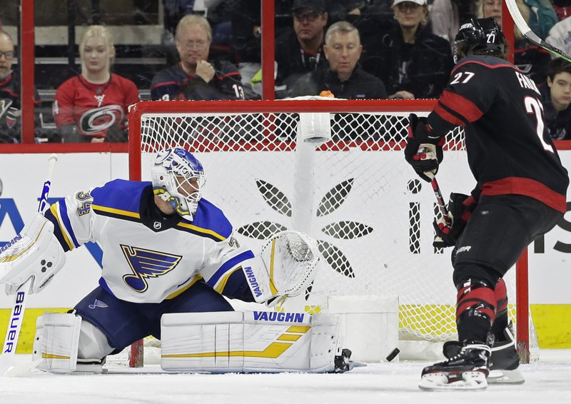Carolina Hurricanes' Justin Faulk (27) looks on as St. Louis Blues goalie Jake Allen (34) misses a goal by Hurricanes' Justin Williams, not shown, during the first period of an NHL hockey game in Raleigh, N. (AP Photo/Gerry Broome)