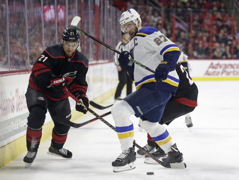 Carolina Hurricanes' Nino Niederreiter (21), of the Czech Republic, and St. Louis Blues' Alex Pietrangelo (27) chase the puck during the first period of an NHL hockey game in Raleigh, N. (AP Photo/Gerry Broome)