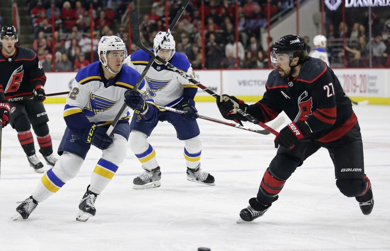 St. Louis Blues' Mackenzie MacEachern (62) and Carolina Hurricanes' Justin Faulk (27) skate for the puck during the first period of an NHL hockey game in Raleigh, N. (AP Photo/Gerry Broome)