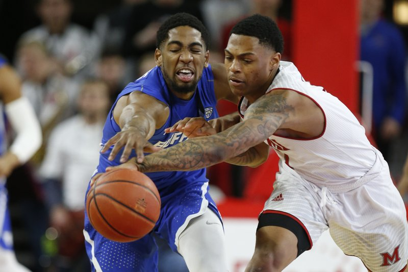 Buffalo guard CJ Massinburg, left, fights for control of the ball with Miami (Ohio) guard Nike Sibande, right, during the first half of an NCAA college basketball game, Friday, March 1, 2019, in Oxford, Ohio. (AP Photo/Gary Landers)