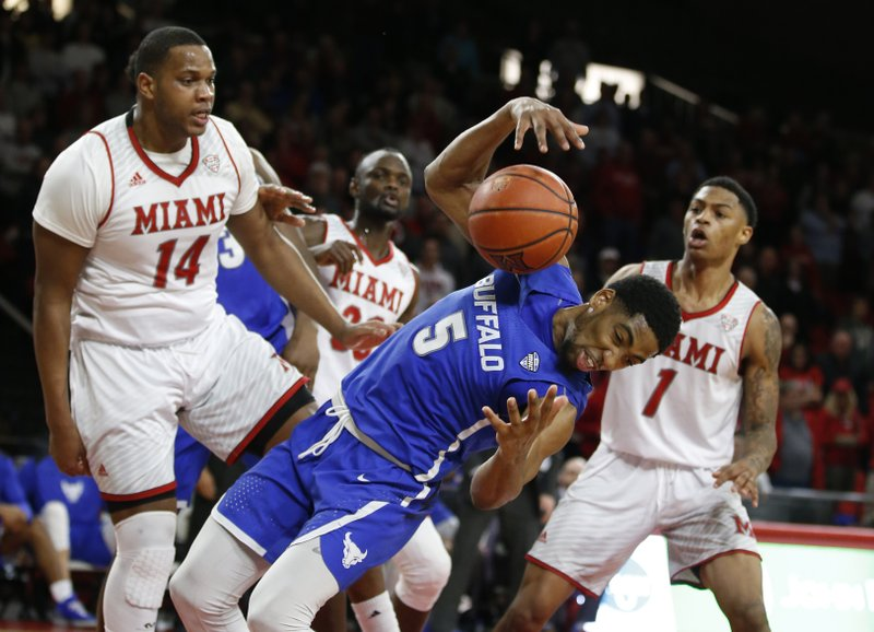 Buffalo guard CJ Massinburg (5) grabs a rebound in between Miami (Ohio) forward Bam Bowman (14) and Nike Sibande (1) during the second half of an NCAA college basketball game, Friday, March 1, 2019, in Oxford, Ohio. (AP Photo/Gary Landers)