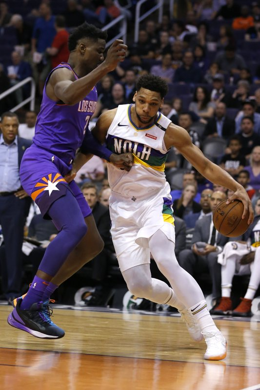 New Orleans Pelicans center Jahlil Okafor (8) drives on Phoenix Suns center Deandre Ayton in the first half during an NBA basketball game, Friday, March 1, 2019, in Phoenix. (AP Photo/Rick Scuteri)