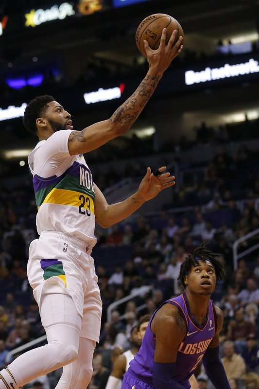 New Orleans Pelicans forward Anthony Davis (23) drives past Phoenix Suns guard Elie Okobo in the first half during an NBA basketball game, Friday, March 1, 2019, in Phoenix. (AP Photo/Rick Scuteri)