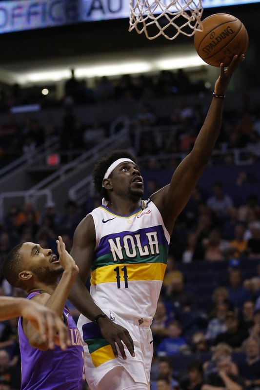 New Orleans Pelicans guard Jrue Holiday (11) drives by Phoenix Suns guard Elie Okobo in the first half during an NBA basketball game, Friday, March 1, 2019, in Phoenix. (AP Photo/Rick Scuteri)
