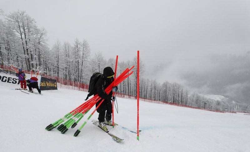 Poles marking the course are being taken out as a training session for a women's downhill race of the alpine ski World Cup, in Rosa Khutor, Russia, was cancelled due to adverse weather conditions Friday, March 1, 2019. (AP Photo/Gabriele Facciotti)