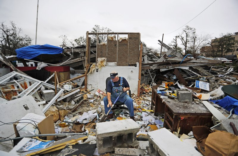 Patrick Muth sifts through debris in what used to be his office of his fifth-generation plumbing business he continues to operate in Panama City, Florida, Wednesday, Jan. (AP Photo/David Goldman)