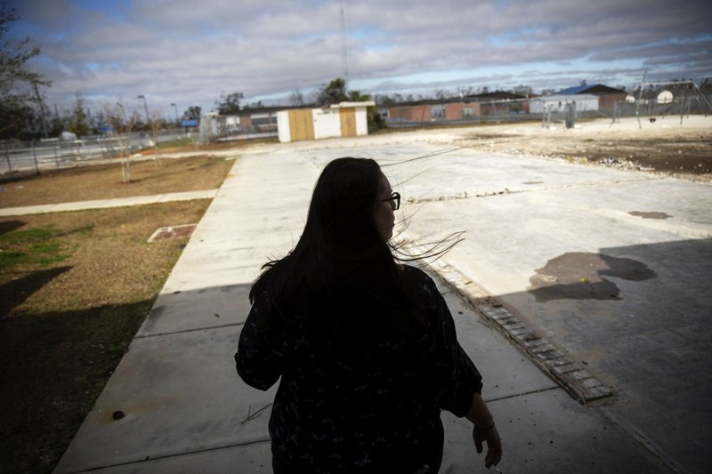 Ilea Faircloth, principal of Springfield Elementary School walks across a bare foundation where classrooms were destroyed by Hurricane Michael and since torn down in Panama City, Fla, Thursday, Jan. (AP Photo/David Goldman)