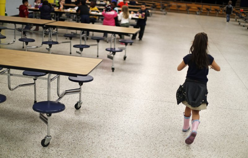 A student walks past empty seats in the Northside Elementary School cafeteria during lunchtime in Panama City, Fla, Thursday, Jan. (AP Photo/David Goldman)
