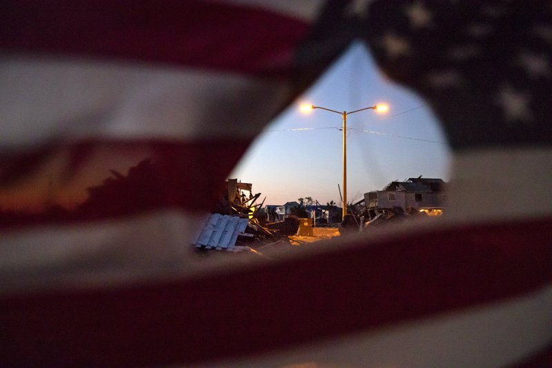 A newly installed street lamp stands amidst the debris from Hurricane Michael as an American flag blows in the wind in Mexico Beach, Fla, Thursday, Jan. (11.5 million cubic meters) of sheet-rock, insulation, tree limbs and appliances strewn everywhere by the storm. (AP Photo/David Goldman)