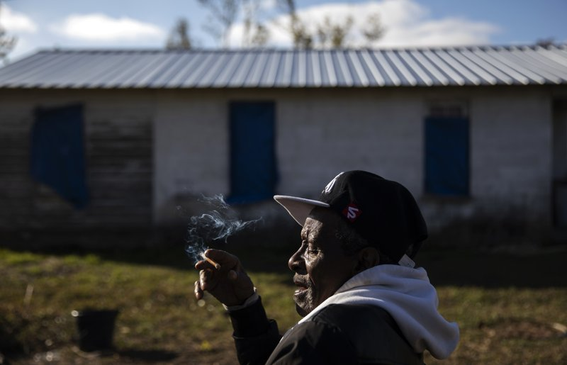 Bimyall Leroy Burke smokes a cigarette outside a damaged home in the neighborhood where he now resides in a Federal Emergency Management Agency trailer in Panama City, Fla, Thursday, Jan. (AP Photo/David Goldman)