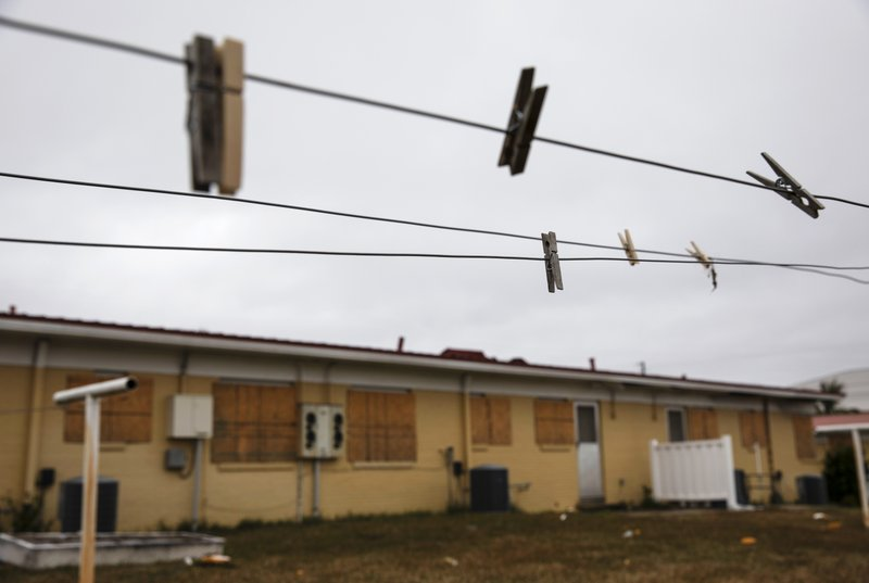 Clothespins hang on a line outside a boarded up housing development damaged from Hurricane Michael in Panama City, Fla, Thursday, Jan. (AP Photo/David Goldman)