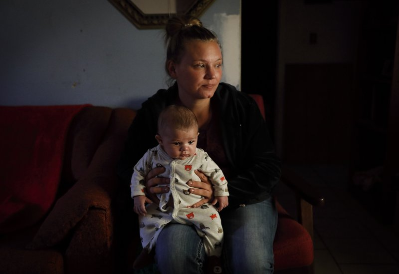 Lorrainda Smith holds her three-month-old son Luke in her mother's house where she is now sleeping on the couch after moving in with her husband and four children in Panama City, Fla, Friday, Jan. (AP Photo/David Goldman)