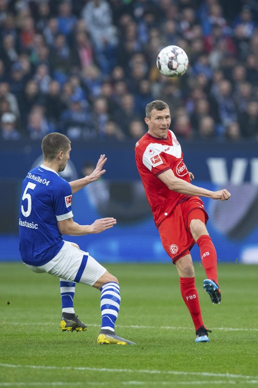 Duesseldorf's Oliver Fink, right, and Schalke's Matija Nastasic, left, challenge for the ball during the German Bundesliga soccer match between FC Schalke 04 and Fortuna Duesseldorf in Gelsenkirchen, Germany, Saturday, March 2, 2019. (Guido Kirchner/dpa via AP)