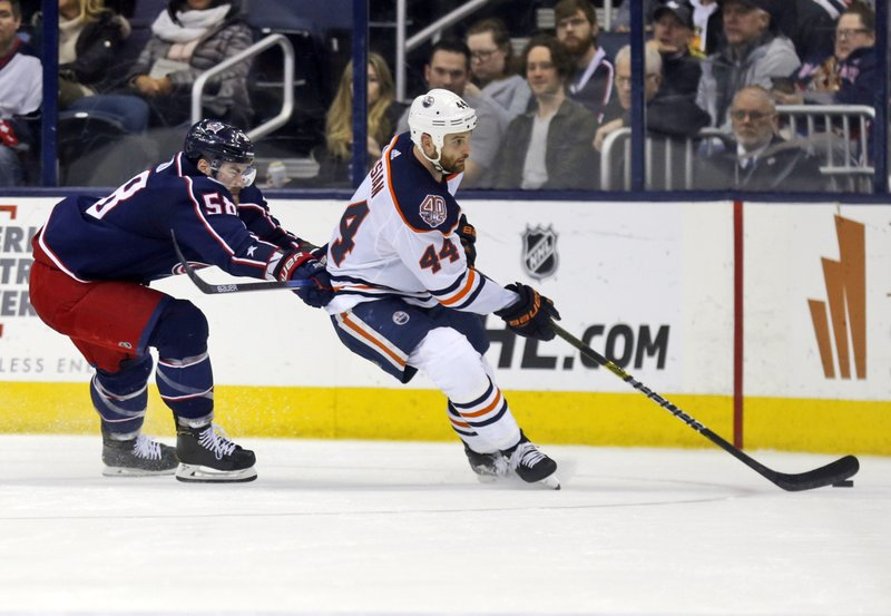 Edmonton Oilers forward Zack Kassian, left, controls the puck against Columbus Blue Jackets defenseman David Savard during the second period of an NHL hockey game in Columbus, Ohio, Saturday, March 2, 2019. (AP Photo/Paul Vernon)