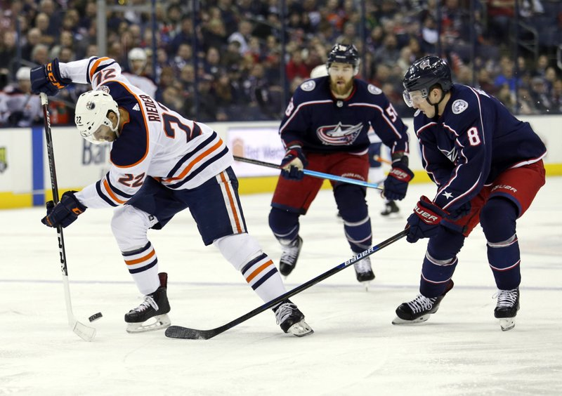 Edmonton Oilers forward Tobias Rieder, left, of Germany, settles the puck against Columbus Blue Jackets defenseman David Savard, center, and defenseman Zach Werenski during the first period of an NHL hockey game in Columbus, Ohio, Saturday, March 2, 2019. (AP Photo/Paul Vernon)