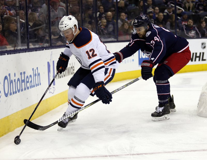Edmonton Oilers forward Colby Cave, left, controls the puck against Columbus Blue Jackets defenseman Adam McQuaid during the first period of an NHL hockey game in Columbus, Ohio, Saturday, March 2, 2019. (AP Photo/Paul Vernon)