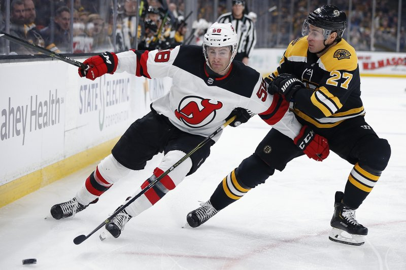 New Jersey Devils' Kevin Rooney (58) and Boston Bruins' John Moore (27) battle for the puck during the first period of an NHL hockey game in Boston, Saturday, March 2, 2019. (AP Photo/Michael Dwyer)