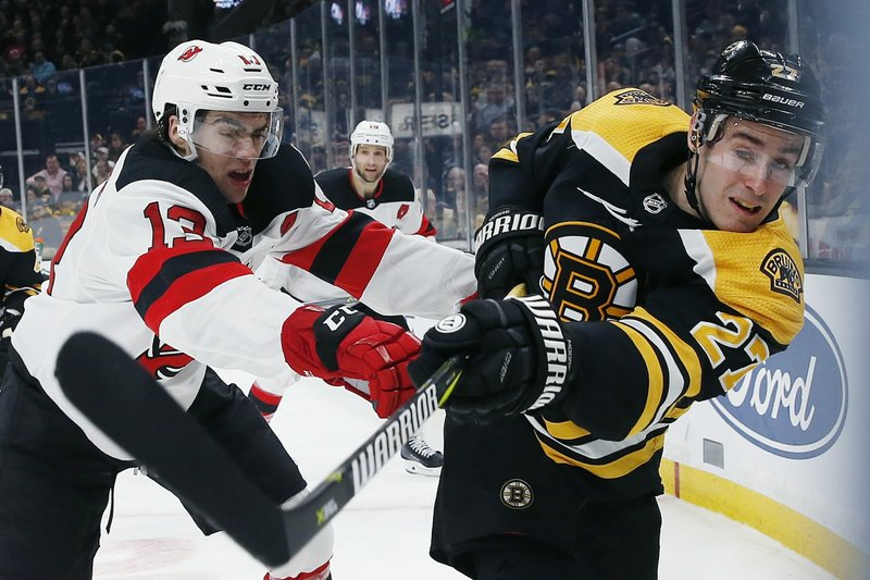 Boston Bruins' John Moore (27) and New Jersey Devils' Nico Hischier (13) battle along the boards during the first period of an NHL hockey game in Boston, Saturday, March 2, 2019. (AP Photo/Michael Dwyer)