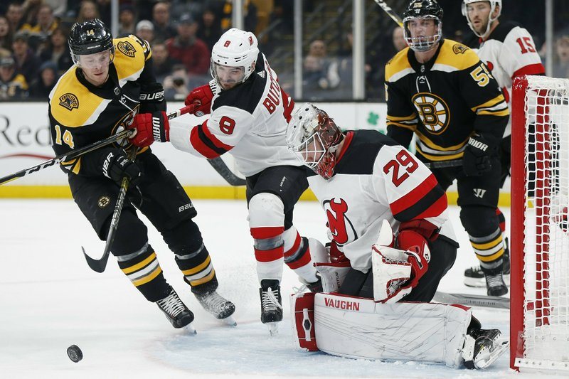 New Jersey Devils' Will Butcher (8) keeps Boston Bruins' Chris Wagner (14) away from the rebound off Mackenzie Blackwood (29) during the second period of an NHL hockey game in Boston, Saturday, March 2, 2019. (AP Photo/Michael Dwyer)