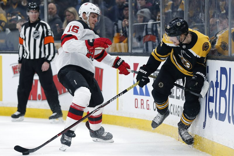 New Jersey Devils' Steven Santini (16) and Boston Bruins' Joakim Nordstrom (20) battle for the puck during the second period of an NHL hockey game in Boston, Saturday, March 2, 2019. (AP Photo/Michael Dwyer)