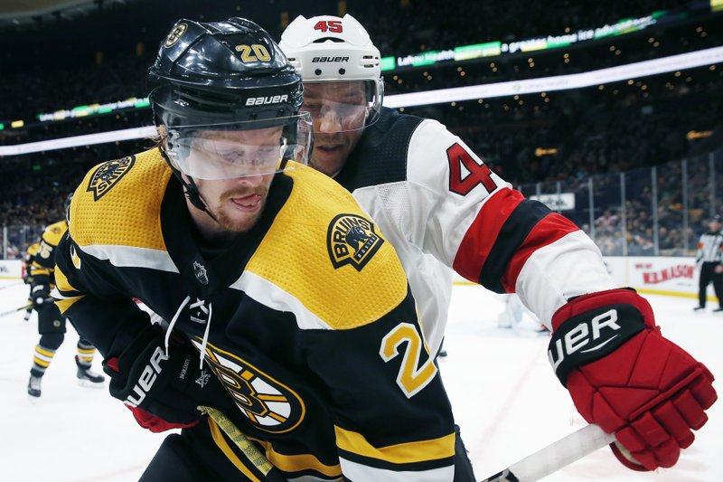 New Jersey Devils' Sami Vatanen (45) battles Boston Bruins' Joakim Nordstrom (20) for the puck during the second period of an NHL hockey game in Boston, Saturday, March 2, 2019. (AP Photo/Michael Dwyer)