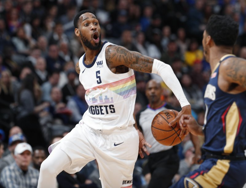 Denver Nuggets guard Will Barton, left, makes a behind-the-back pass to a teammate who then scored, as New Orleans Pelicans guard Elfrid Payton defends during the second half of an NBA basketball game Saturday, March 2, 2019, in Denver. (AP Photo/David Zalubowski)