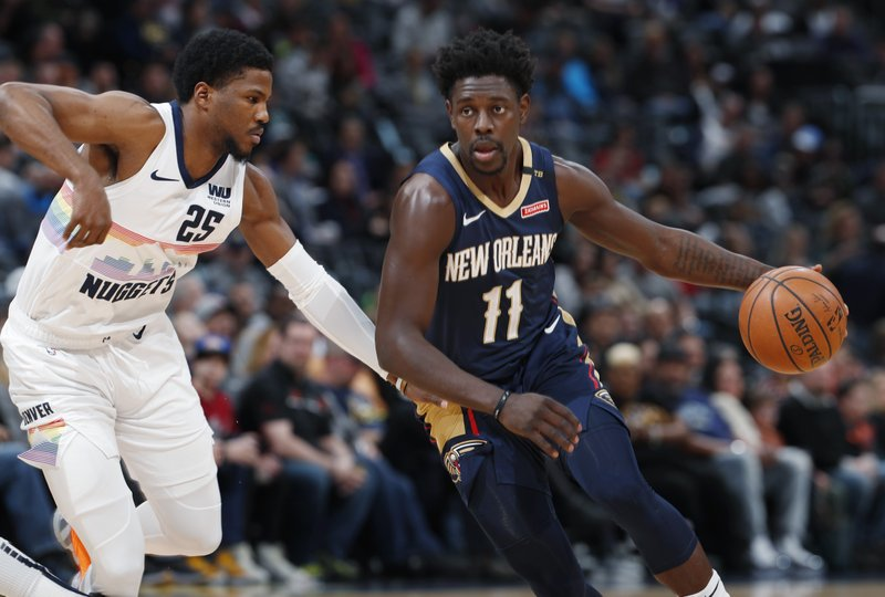 New Orleans Pelicans guard Jrue Holiday, right, drives the lane past Denver Nuggets guard Malik Beasley in the first half of an NBA basketball game Saturday, March 2, 2019, in Denver. (AP Photo/David Zalubowski)