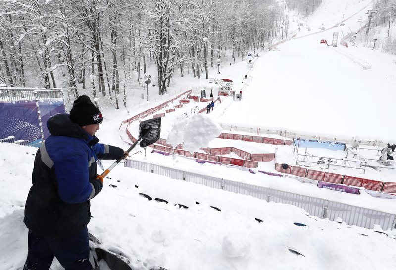 A race official shovels snow from the stands after a women's World Cup super-G was cancelled due to bad weather conditions, in Rosa Khutor, Russia, Saturday, March 2, 2019. (AP Photo/Gabriele Facciotti)