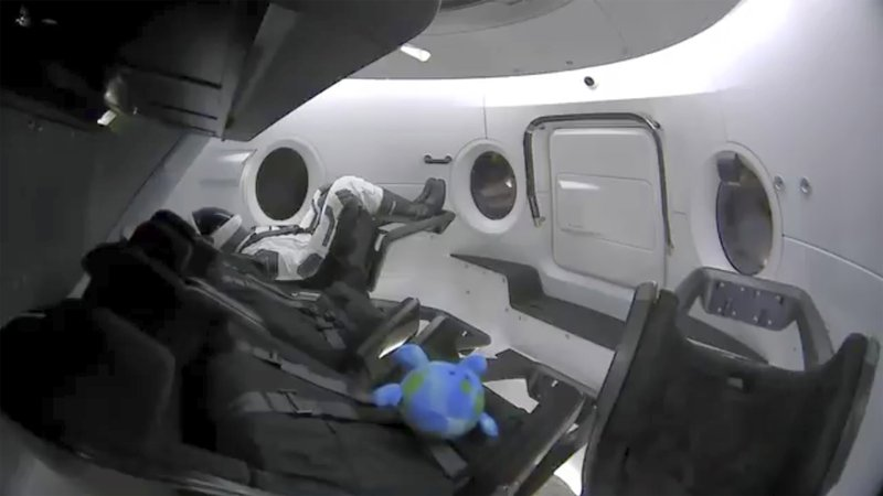 This photo provided by SpaceX shows a life-size test dummy along with a toy that is floating in the Dragon capsule as the capsule made orbit on Saturday, March 2, 2019. (SpaceX via AP)