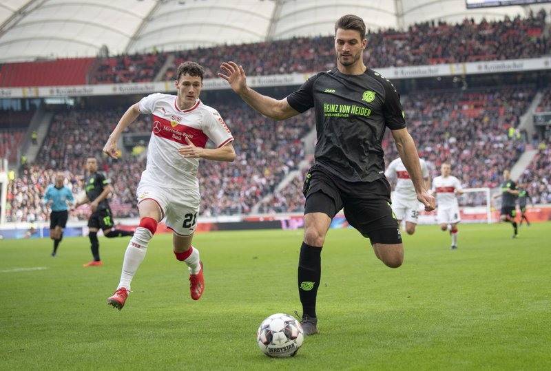 Stuttgart's Benjamin Pavard , left, and Hannovers Hendrik Weydandt, right, challenge for the ball during the German Bundesliga soccer match between VfB Stuttgart and Hannover 96 in Stuttgart, Germany, Sunday, March 3, 2019. (Sebastian Gollnow/dpa via AP)