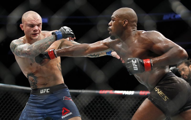 Jon Jones, right, takes a swing at Anthony Smith during a light heavyweight mixed martial arts title bout at UFC 235, Saturday, March 2, 2019, in Las Vegas. (AP Photo/John Locher)