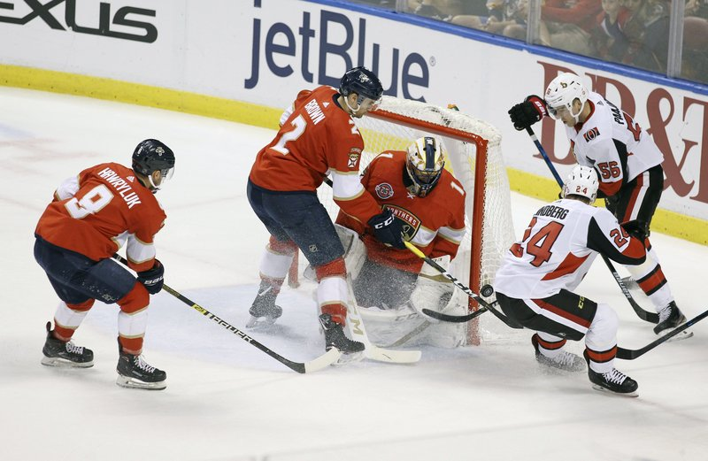 Ottawa Senators' Oscar Lindberg (24) reaches for the puck with Magnus Paajarvi (56) as Florida Panthers goalkeeper Roberto Luongo (1), Jayce Hawryluk (8) and Josh Brown (2) defend during the first period of an NHL hockey game, Sunday, March 3, 2019, in Sunrise, Fla. (AP Photo/Luis M. Alvarez)