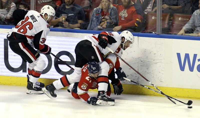 Ottawa Senators' Christian Wolanin, top right, and Colin White (36) try to control the puck against Florida Panthers' Vincent Trocheck, bottom, during the third period of an NHL hockey game, Sunday, March 3, 2019, in Sunrise, Fla. (AP Photo/Luis M. Alvarez)