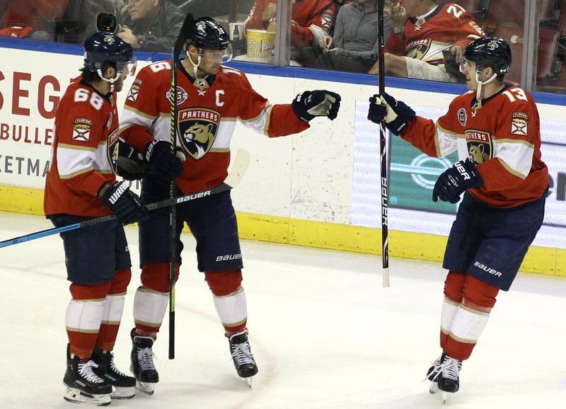 Florida Panthers' Aleksander Barkov, center, celebrates with teammates Mike Hoffman (68) and Mark Pysyk (13) after scoring a goal against the Ottawa Senators during the first period of an NHL hockey game, Sunday, March 3, 2019, in Sunrise, Fla. (AP Photo/Luis M. Alvarez)