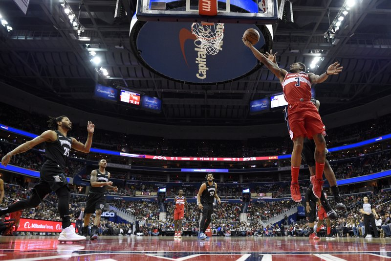 Washington Wizards guard Bradley Beal (3) goes to the basket against Minnesota Timberwolves guard Derrick Rose (25), center Karl-Anthony Towns (32) and guard Jeff Teague, second from left, during the first half of an NBA basketball game, Sunday, March 3, 2019, in Washington. (AP Photo/Nick Wass)