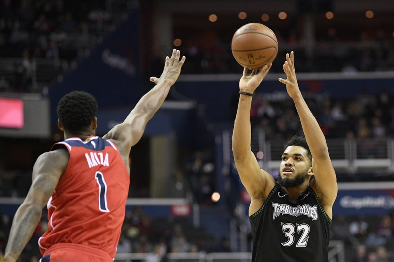Minnesota Timberwolves center Karl-Anthony Towns (32) shoots against Washington Wizards forward Trevor Ariza (1) during the first half of an NBA basketball game, Sunday, March 3, 2019, in Washington. (AP Photo/Nick Wass)