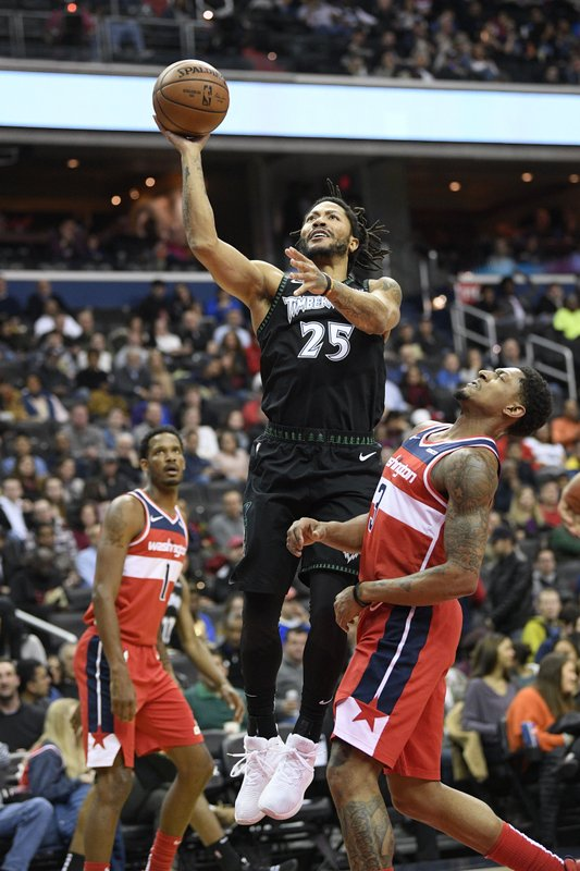 Minnesota Timberwolves guard Derrick Rose (25) goes to the basket against Washington Wizards guard Bradley Beal (3) and forward Trevor Ariza (1) during the first half of an NBA basketball game, Sunday, March 3, 2019, in Washington. (AP Photo/Nick Wass)
