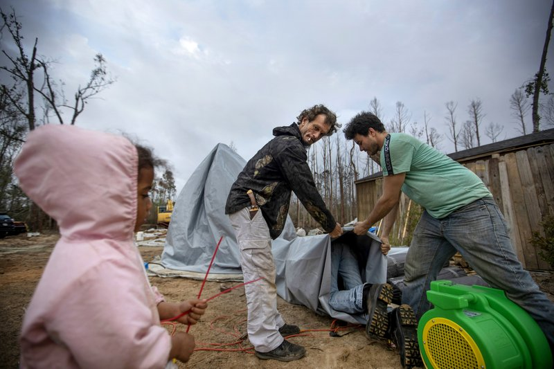 Jeff Dunn, left, and Lance Gomez help construct a dome shelter in Diahnn