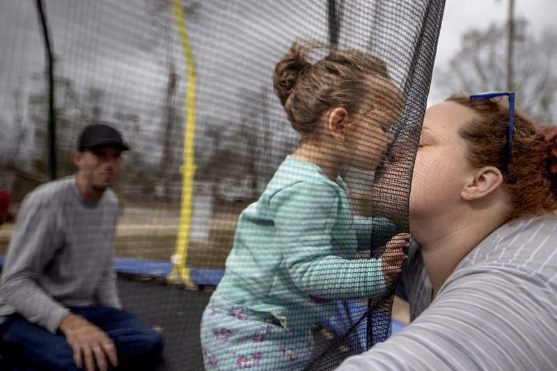 Mystie Gregory, right, kisses her twenty-month-old daughter Neala as her fiancé Gary LaPlant looks on while playing on a trampoline in the backyard where several local residents are living in tents after becoming homeless from Hurricane Michael in Youngstown, Fla, Wednesday, Jan. (AP Photo/David Goldman)