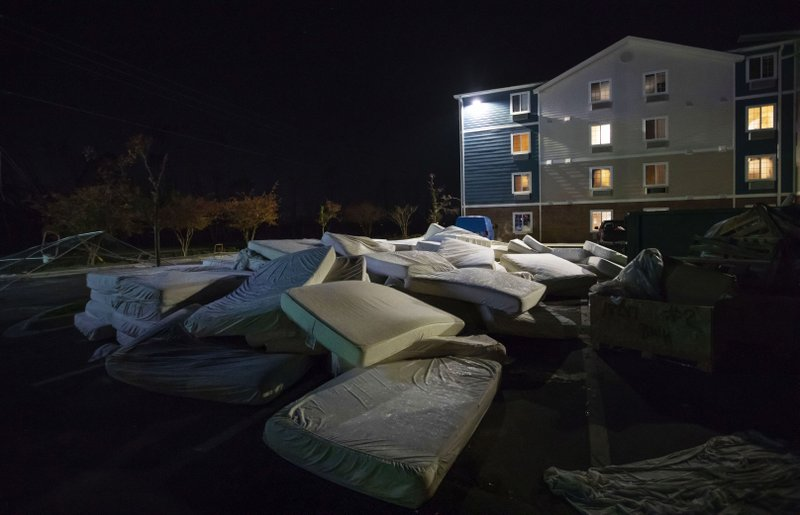 Mattresses are discarded from a damaged hotel from Hurricane Michael which is closed during renovation in Panama City, Fla, Thursday, Jan. (AP Photo/David Goldman)