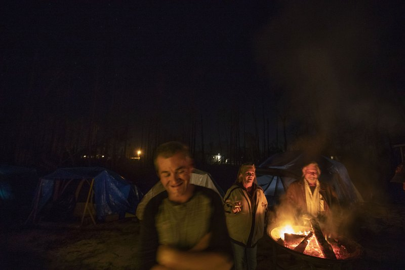 Gene Hogan laughs around a campfire in the backyard of Sam, right, and Diahnn