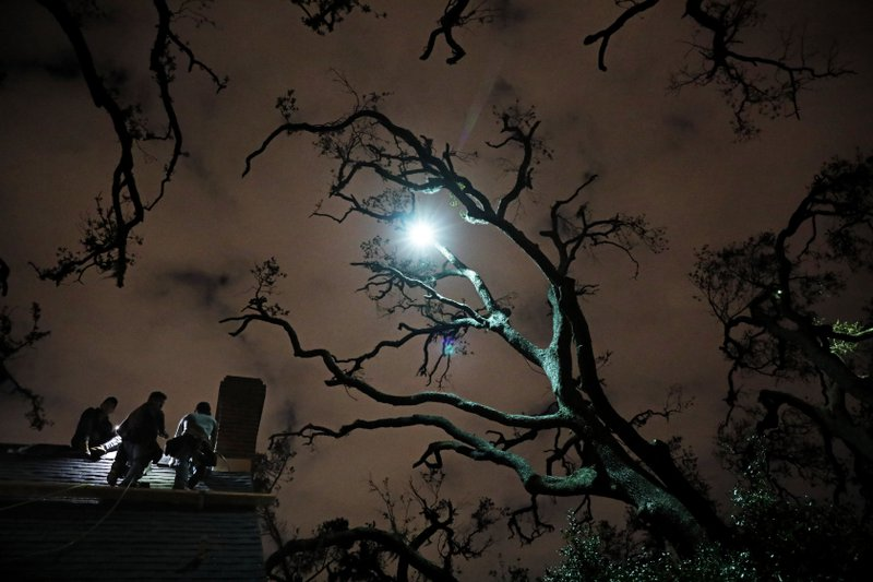 Workers repair a roof at night under trees left bare by Hurricane Michael in Panama City, Fla, Tuesday, Jan. (AP Photo/David Goldman)