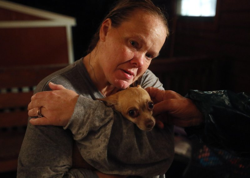 Lori Hogan, hugs her dog, Boo Boo, after losing him during a rain storm which brought on a panic attack for Hogan who is currently living in a tent in a backyard months after Hurricane Michael hit in Youngstown, Fla, Wednesday, Jan. (AP Photo/David Goldman)
