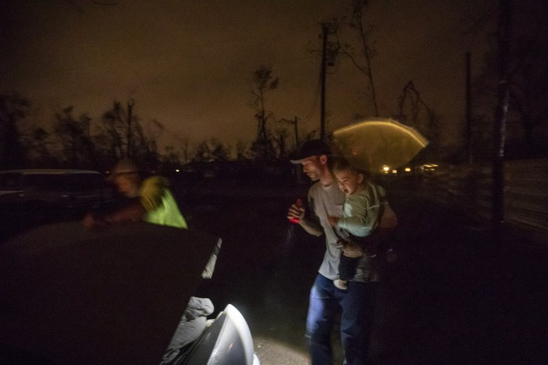 Twenty-month-old Neala Clark cries as her mother's fiancé, Gary LaPlant, loads their personal belongings from the tent they're living in into a car taking them to a halfway home LaPlant found for them in the middle of a rain storm in Youngstown, Fla, Wednesday, Jan. (AP Photo/David Goldman)